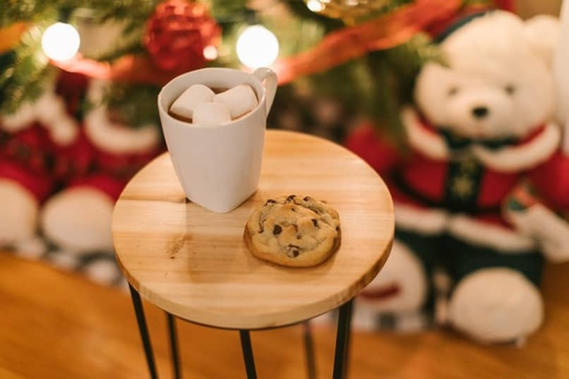 milk and cookies with christmas decorations in the background
